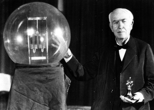 Слева от Эдисона лампа накаливания огромного размера, в руках - компактный вариант