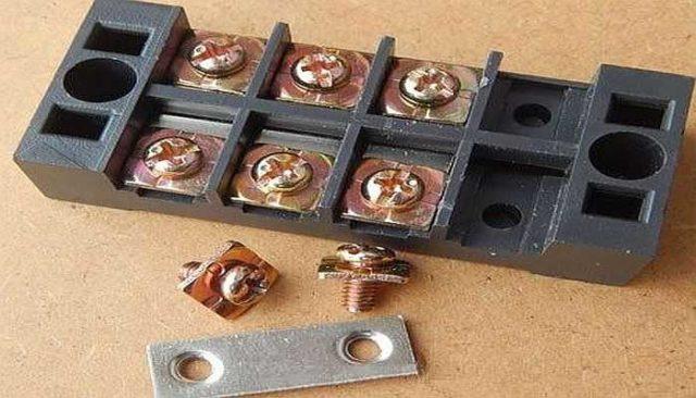 Пластина из белого металла располагается внизу и соединяет подключенные провода, винты с квадратными шайбами обеспечивают качественный контакт