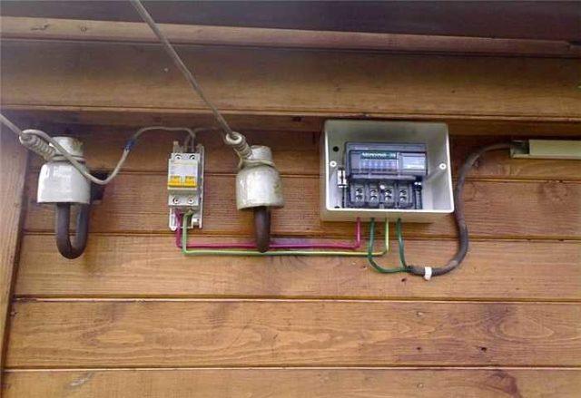 Один из вариантов подключения: счетчик в боксе, автомат - на улице, но под крышей... Мягко говоря, не лучшее решение. Автоматический выключатель, как и счетчик, должен быть защищен от пыли и атмосферных осадков